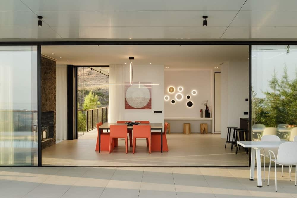 This is a closer look at the dining and kitchen area where the orange chairs stand out. on the far side of this is the large opening that leads to the balcony.