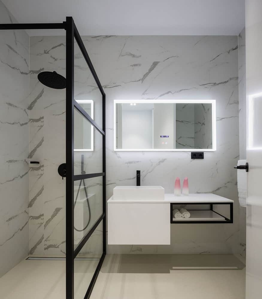 This is the bathroom that has white marble tones n its walls from the modern vanity with the floating sink to the glass-enclosed shower area.