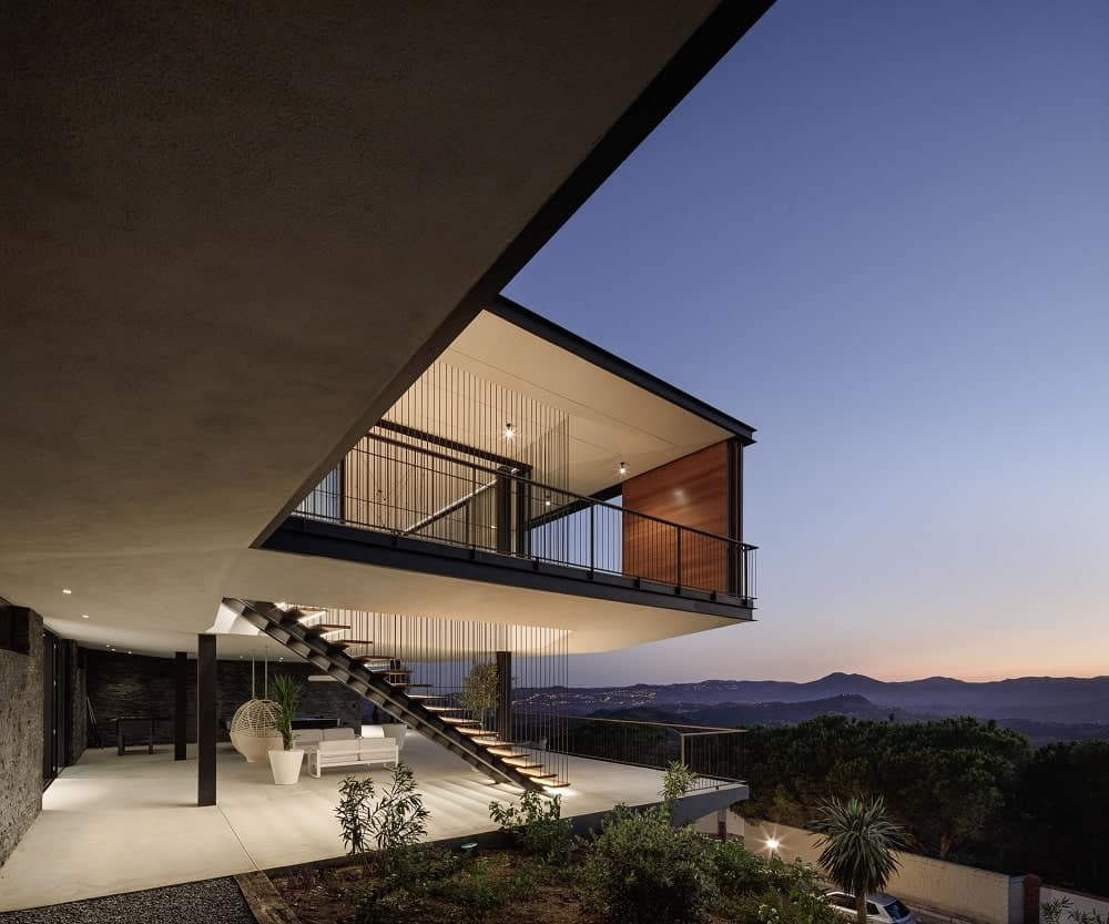This is a look at the side of the house facing the sweeping view of the mountains maximized with a large balcony and a terrace at the ground level. These are then complemented by the warm glow of the lights.