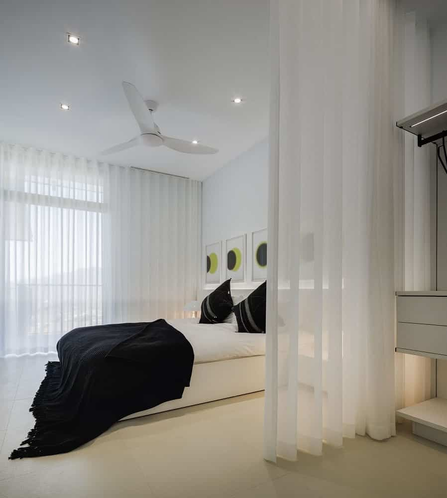 This is the bedroom with a consistent white tone to its bed, walls, ceiling and curtains contrasted by the black pillows and sheets.
