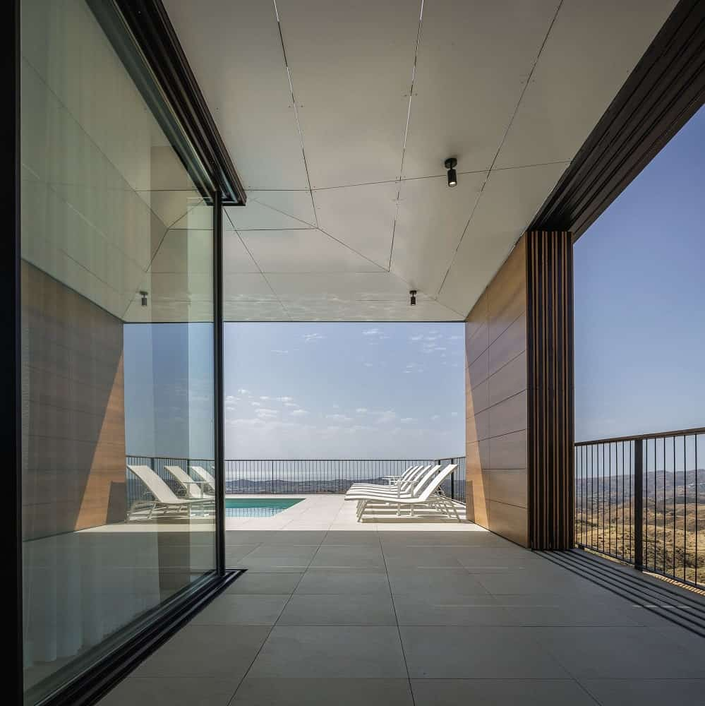This is a balcony on the side of the glass-walled living room leading from the poolside area with a cover and a view.