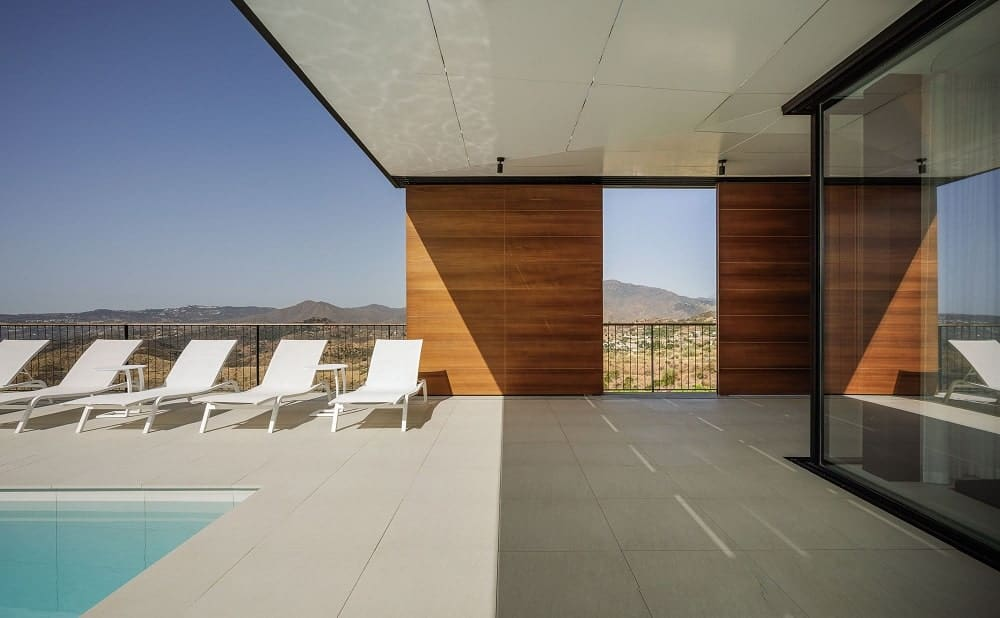 This view of the poolside area showcases the large glass walls of the living room area as well as the large wooden panels at the balcony on the far side.