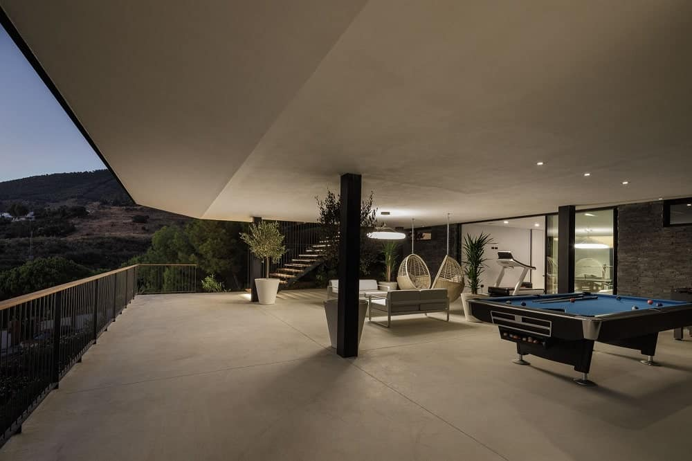 This is the large terrace with a patio area and a game area underneath a cover and warmly light by lights.