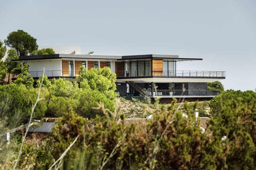 The neutral tones of the house that is augmented by metal and glass are complemented by the surrounding lush landscaping of trees and shrubs.