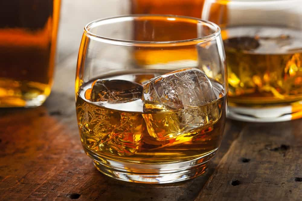 A close look at a couple of glasses with ice cubes and bourbon.