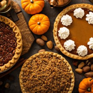 Three various pies adorned by a rustic spread of fresh ingredients.