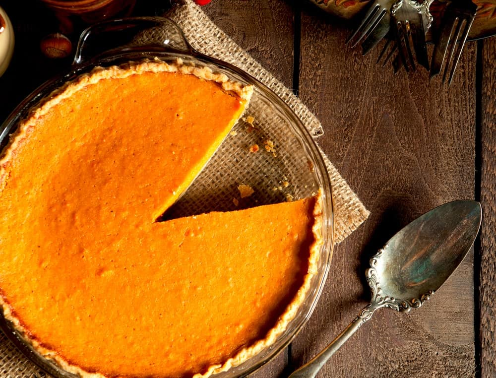 A whole sweet potato pie with a slice missing.