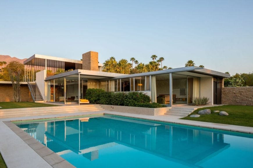 This is a view of the back of the house with a alrge swimming pool and a lush landscape that complements the straight lines and glass walls of the house. Image courtesy of Toptenrealestatedeals.com.