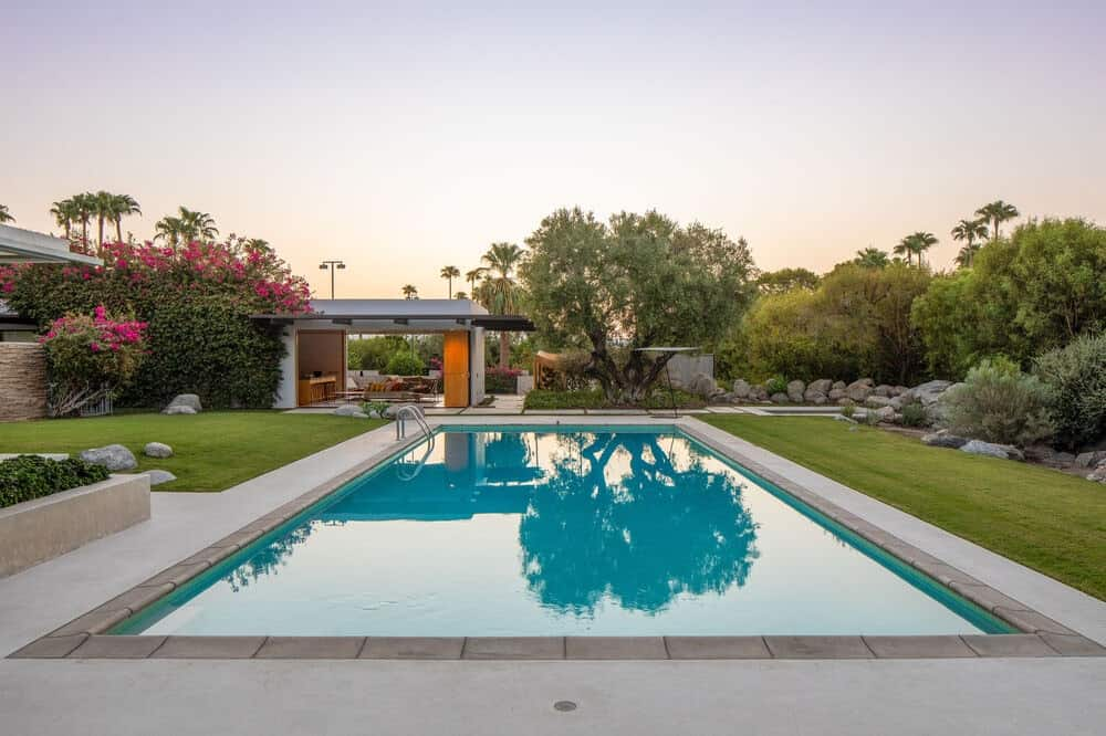 This is a look at the swimming pool from the vantage of the house. You can see here that it has a pool house on the far side adorned with lush landscaping of trees and shrubs. Image courtesy of Toptenrealestatedeals.com.