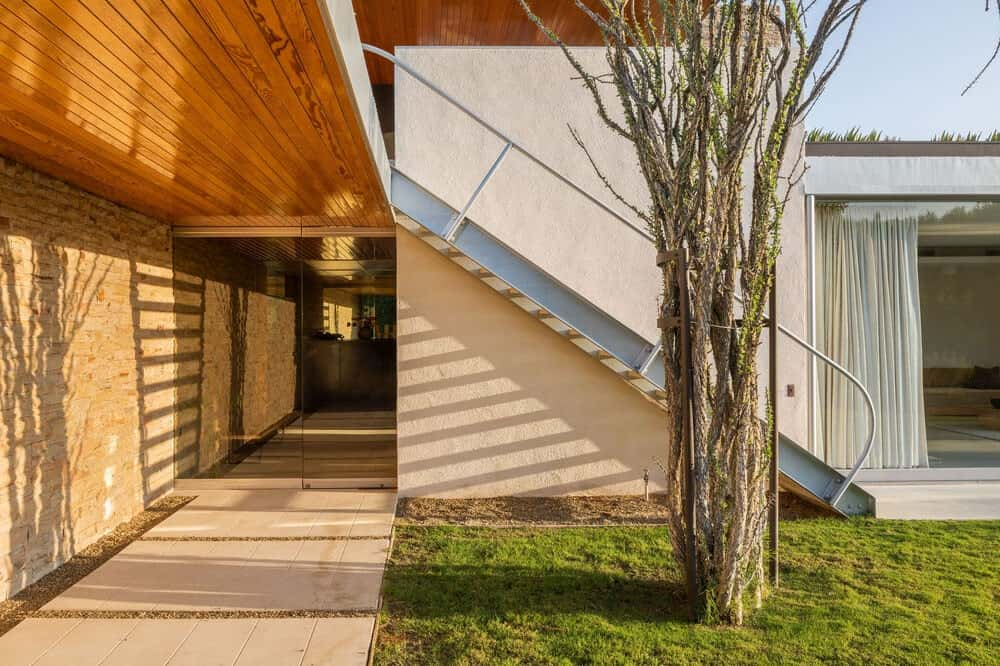 This isde of the house has a green lawn, a staircase and a concrete walkway that goes under the stairs to the other sections of the house. Image courtesy of Toptenrealestatedeals.com.