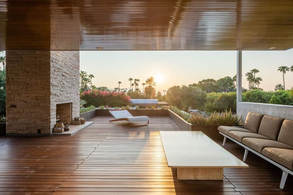 The large balcony has hardwood flooring that matches the ceiling above the sofa as well as planters on the far side. Image courtesy of Toptenrealestatedeals.com.