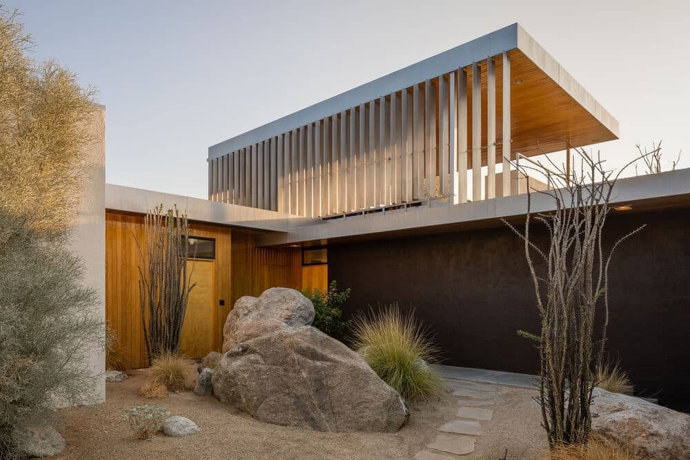 This is a close look at the desert landscaping at the side of the house that goes well with the dark exterior wall. It has a large decorative rock across from the wooden door. Image courtesy of Toptenrealestatedeals.com.