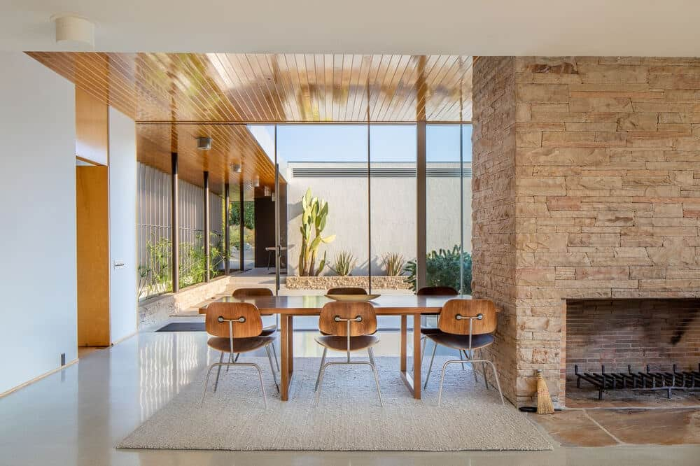 This is the dining area with a large wooden dining table attached to the large stone fireplace paired with wooden chairs. Image courtesy of Toptenrealestatedeals.com.