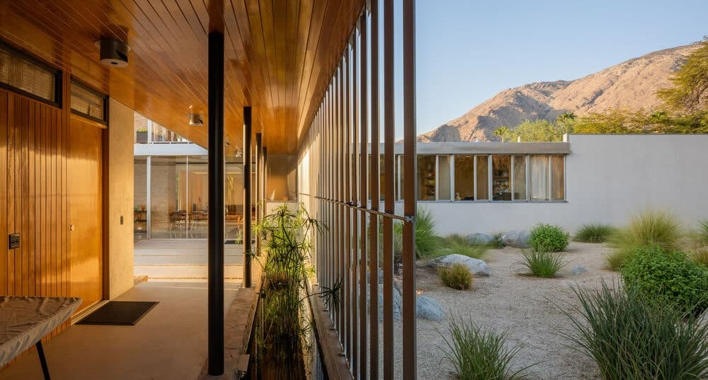 This is a hallway at the side of the house with planters on the side opposite from the desert landscape outside. Image courtesy of Toptenrealestatedeals.com.