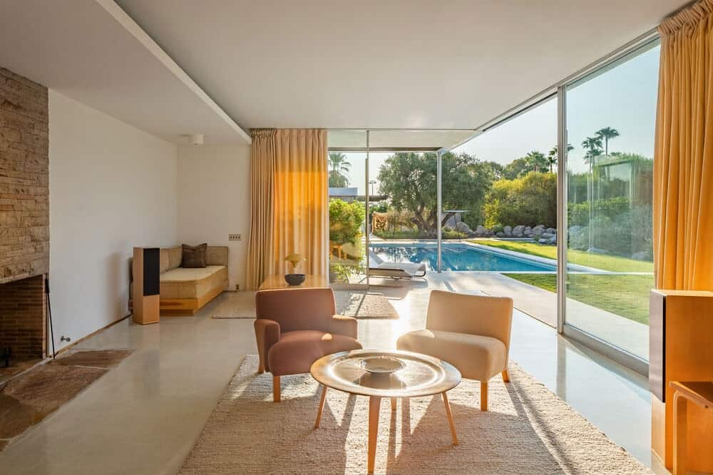 This is the living room area with large glass walls looking over the backyard pool and natural lighting that brightened the spacious room. Image courtesy of Toptenrealestatedeals.com.