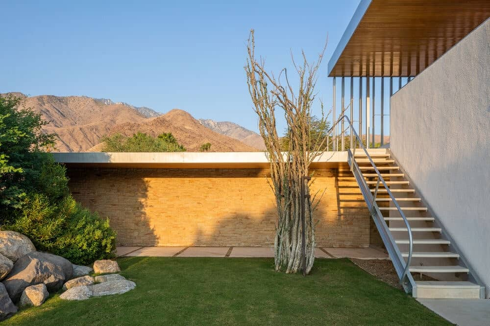 This side of the house has a grass lawn with descorative rocks across from the staircase at the side of the house wall. Image courtesy of Toptenrealestatedeals.com.