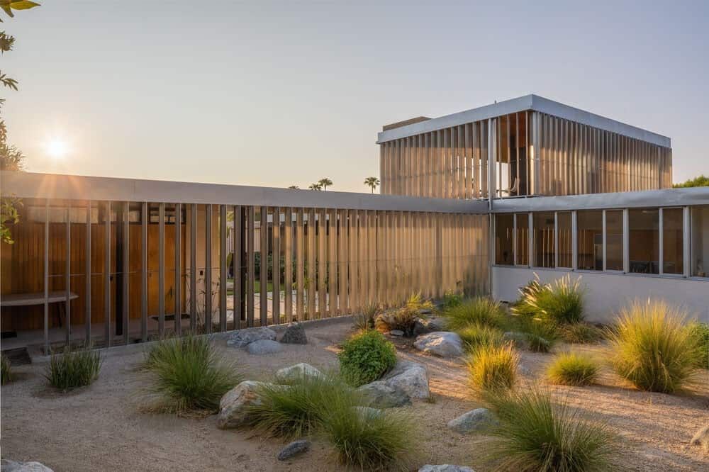 This is a look at the desert garden landscaping with shrubs, rocks and sand that pairs well with the exteriors of the house. Image courtesy of Toptenrealestatedeals.com.