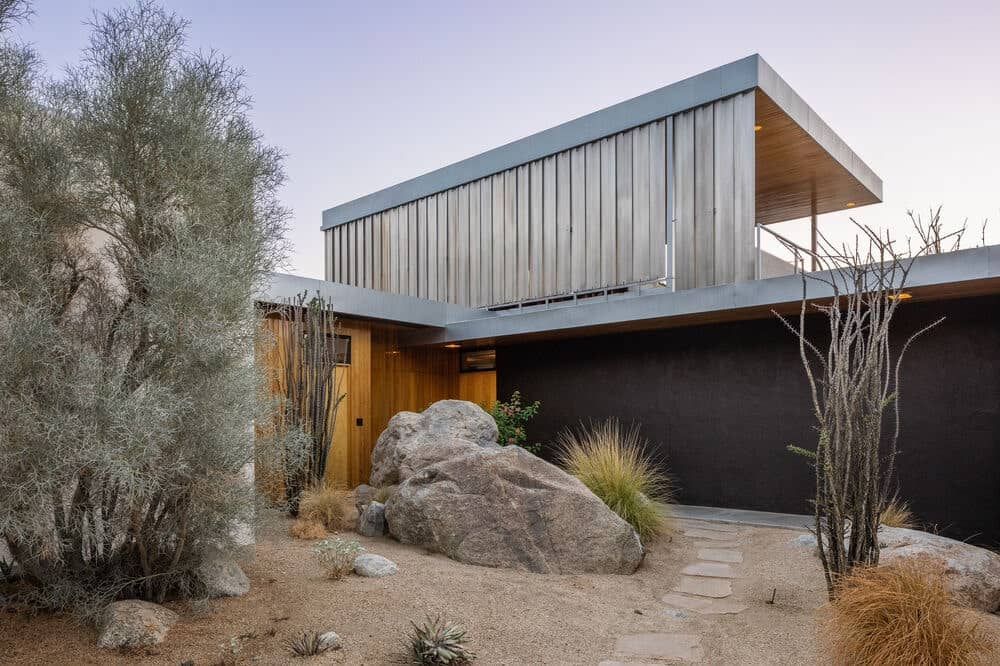This is a close look at the desert landscaping at the side of the house that goes well with the dark exterior wall. Image courtesy of Toptenrealestatedeals.com.