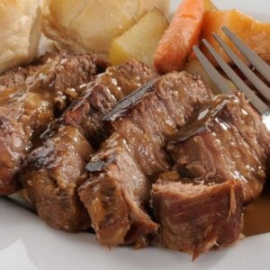 A plate of pot roast and gravy with a side of vegetables and bread.