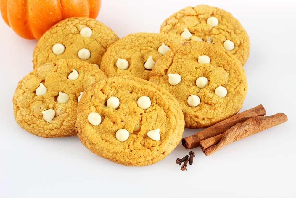 Pumpkin white chocolate chip cookies beside cinnamon sticks.