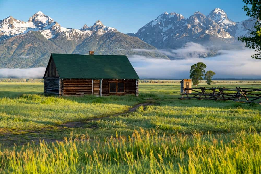 A rustic home and field perfect for homesteading with a mountain view.