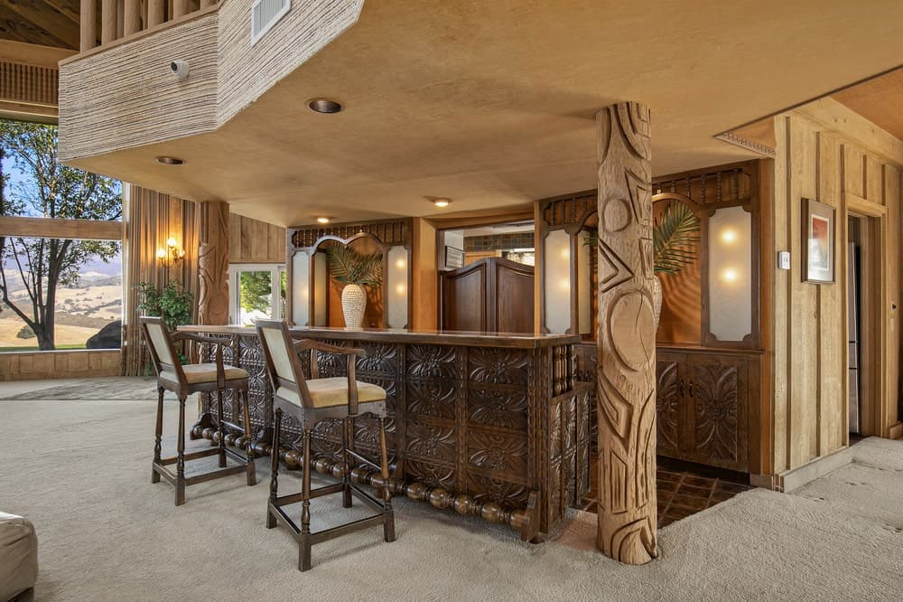 This is the bar that has a large dark wooden bar with carvings that matches with the pillars. Image courtesy of Toptenrealestatedeals.com.