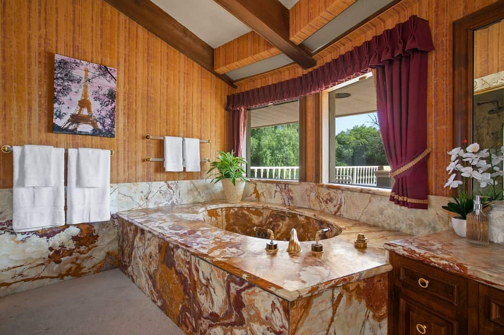 The bathroom has a large bathtub housed in a large brown marble structure that matches perfectly with the wood-paneled walls and beamed ceiling. Image courtesy of Toptenrealestatedeals.com.