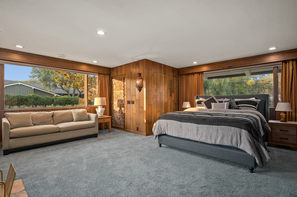 This is the spacious bedroom that has a large gray bed and a beige sofa complemented by the wood-paneled walls and gray carpeting. Image courtesy of Toptenrealestatedeals.com.