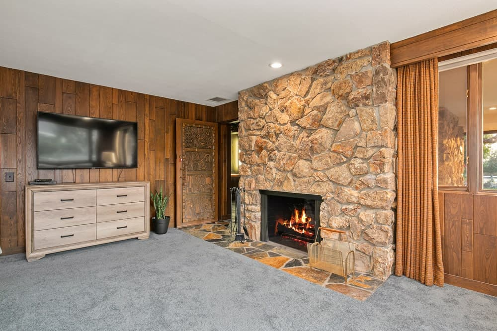 This is the large mosaic stone wall across from the bed that houses the fireplace. On the side is the dresser and the wall-mounted TV. Image courtesy of Toptenrealestatedeals.com.