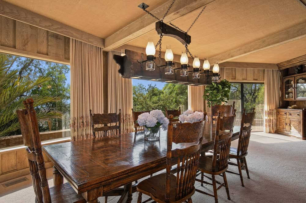 This is the simple dining area of the building with a wooden dining table surrounded by wooden chairs. Image courtesy of Toptenrealestatedeals.com.