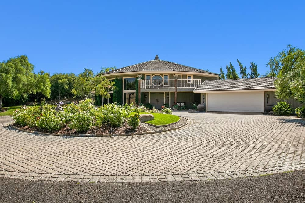 This is the Founder's Building with a large bricked driveway leading to the main entrance and garage door across from the circular garden. Image courtesy of Toptenrealestatedeals.com.