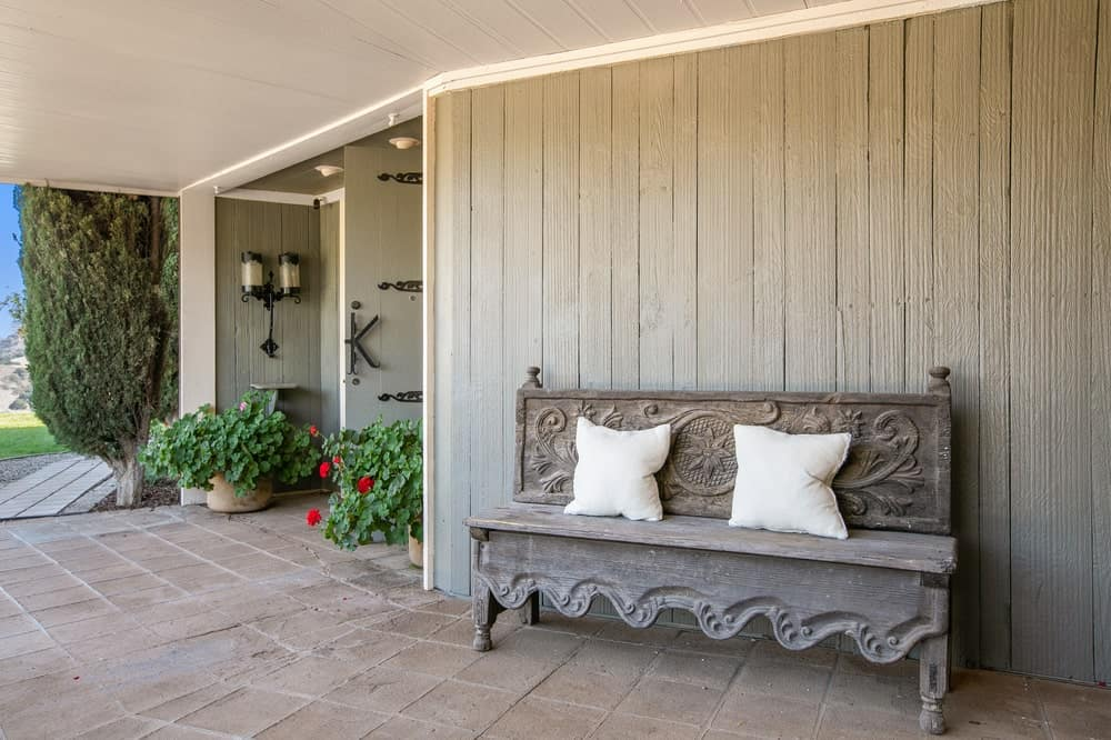 The main entrance of the building is adorned with a decorative wooden bench on the side of the main door that matches well with the gray exteriors. Image courtesy of Toptenrealestatedeals.com.