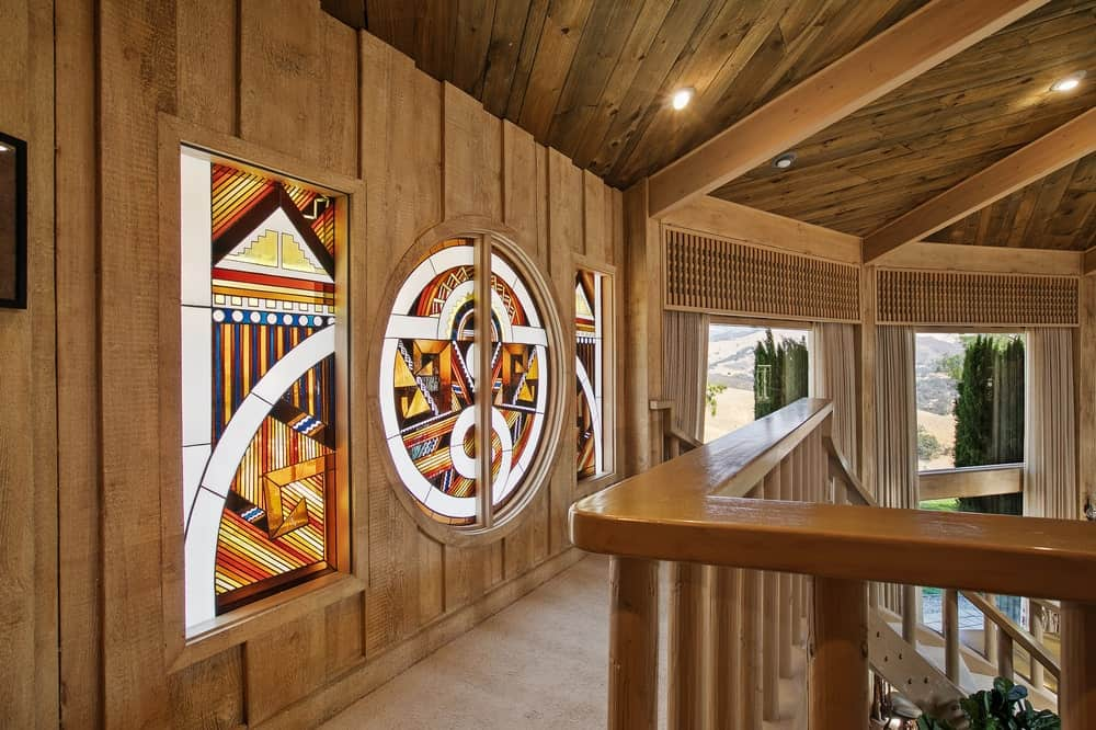 The wooden walls of the second level indoor balcony is adorned with various decors and wall murals. Image courtesy of Toptenrealestatedeals.com.