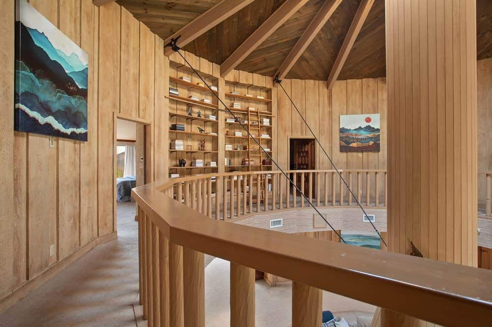 This is a look at the indoor balcony and walkway of the second level that has wooden railings to match the wooden walls with built-in shelves. Image courtesy of Toptenrealestatedeals.com.