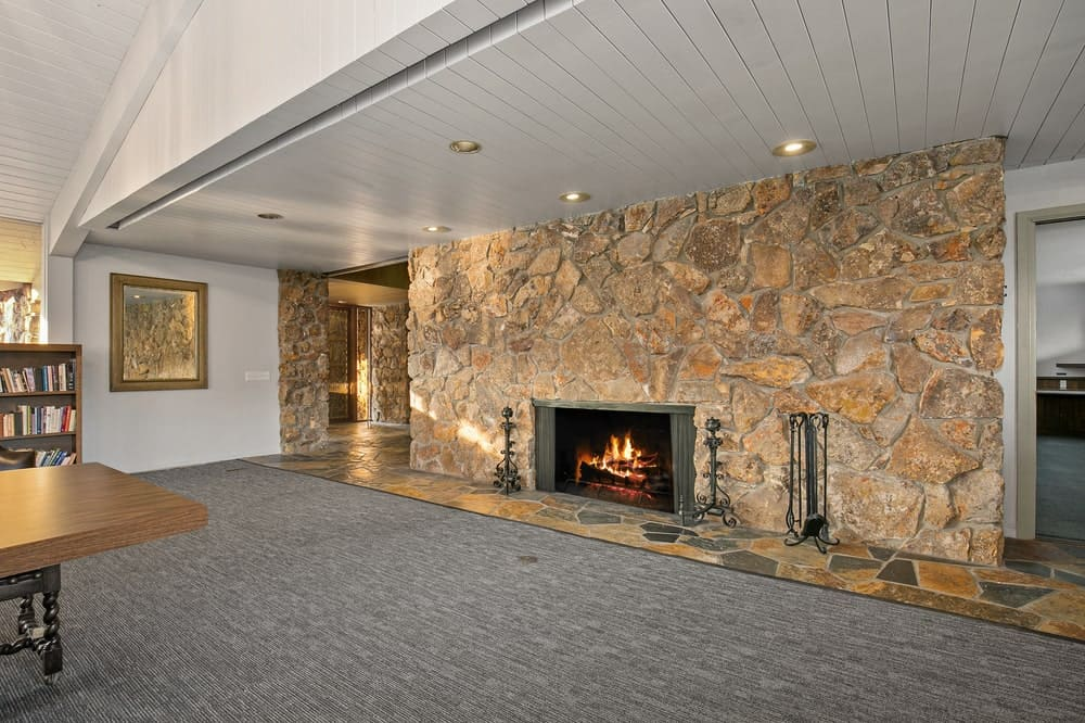 This is the edge of the library interior with a large mosaic stone wall that houses the fireplace. Image courtesy of Toptenrealestatedeals.com.