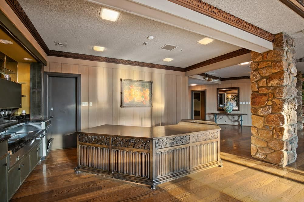 This is the wet bar of the main lodge that has a wooden bar that matches the hardwood flooring and a set of stainless steel kitchenette. Image courtesy of Toptenrealestatedeals.com.