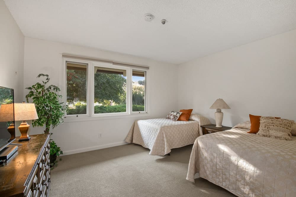 This is a simple bedroom with two beds and a wooden dresser across from them adorned by a table lamp and a potted plant. Image courtesy of Toptenrealestatedeals.com.