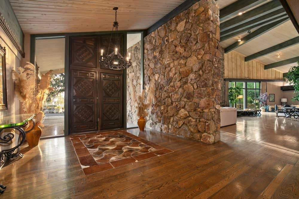 Upon entry of the main lodge, you are welcomed by this foyer that has a large mosaic stone wall on one side and topped with a chandelier that matches the main door. Image courtesy of Toptenrealestatedeals.com.
