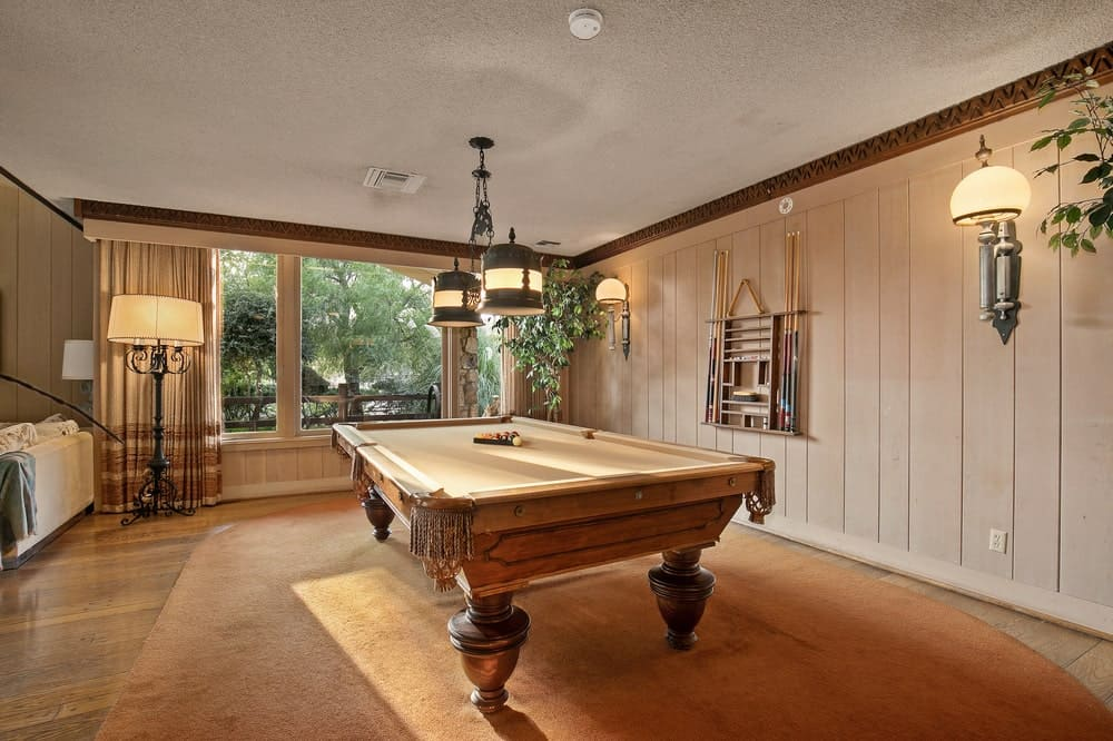 This is a close look at the game room that has a large pool table in the middle that matches the hardwood flooring. Image courtesy of Toptenrealestatedeals.com.