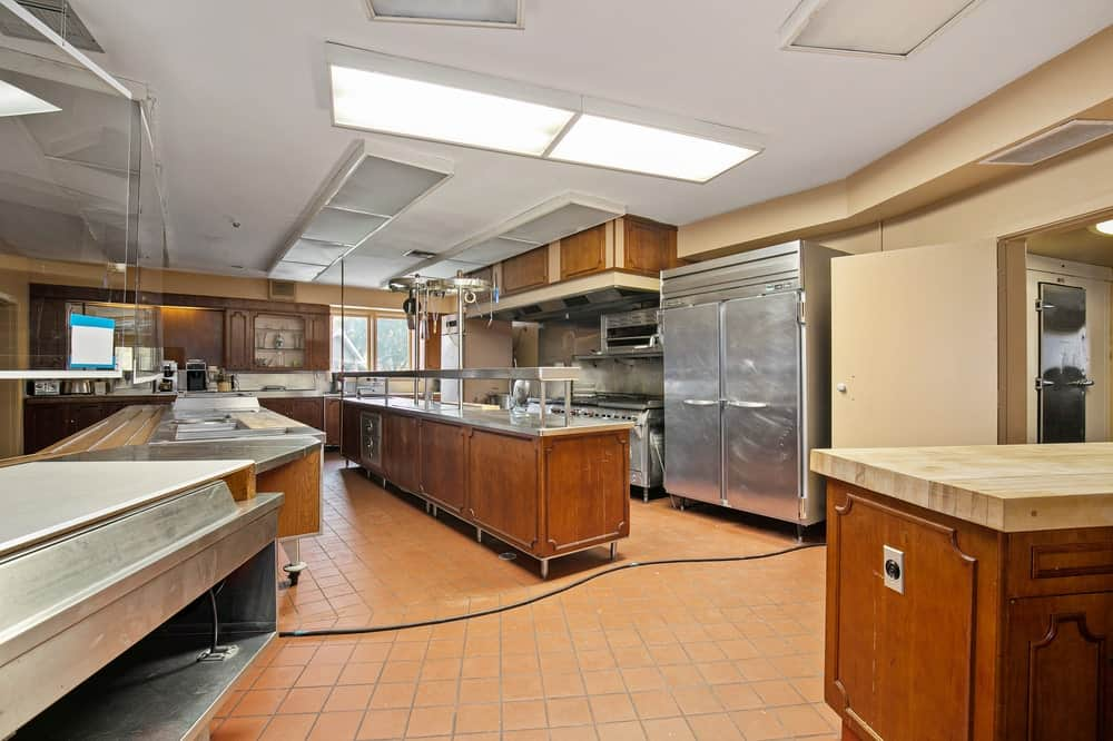 This is the spacious commercial kitchen with a large peninsula, wooden cabinetry and stainless steel structures that house appliances. Image courtesy of Toptenrealestatedeals.com.