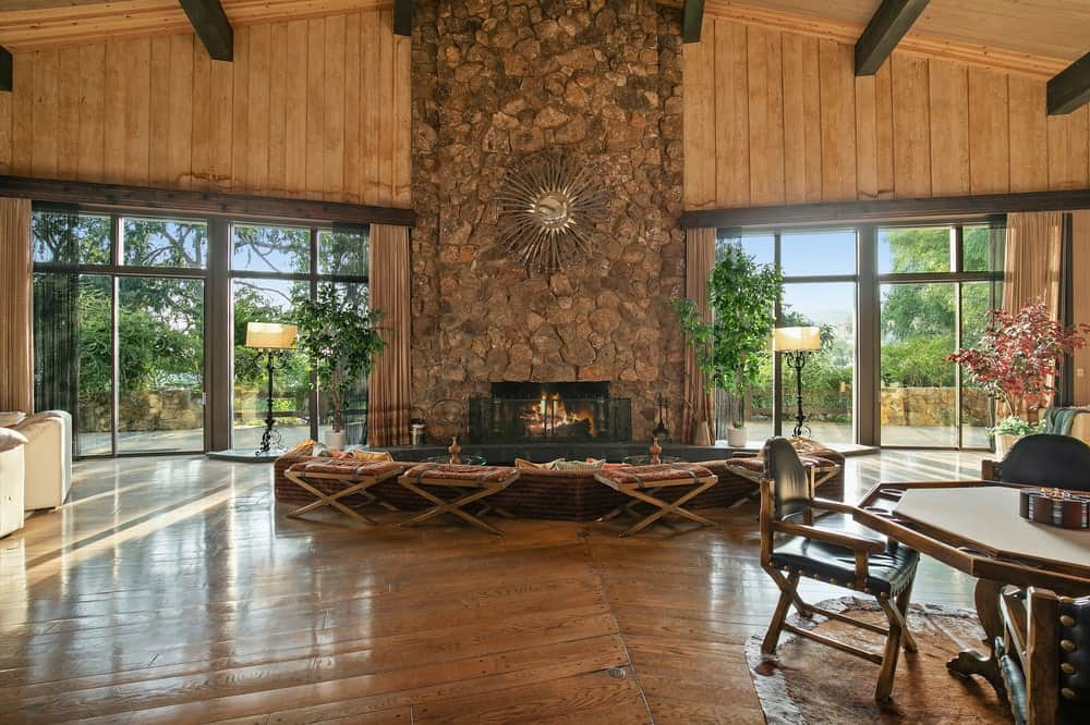 This is a look at the living room area that is facing the massive mosaic stone fireplace on the far side that reaches to the top of the tall ceiling. Image courtesy of Toptenrealestatedeals.com.