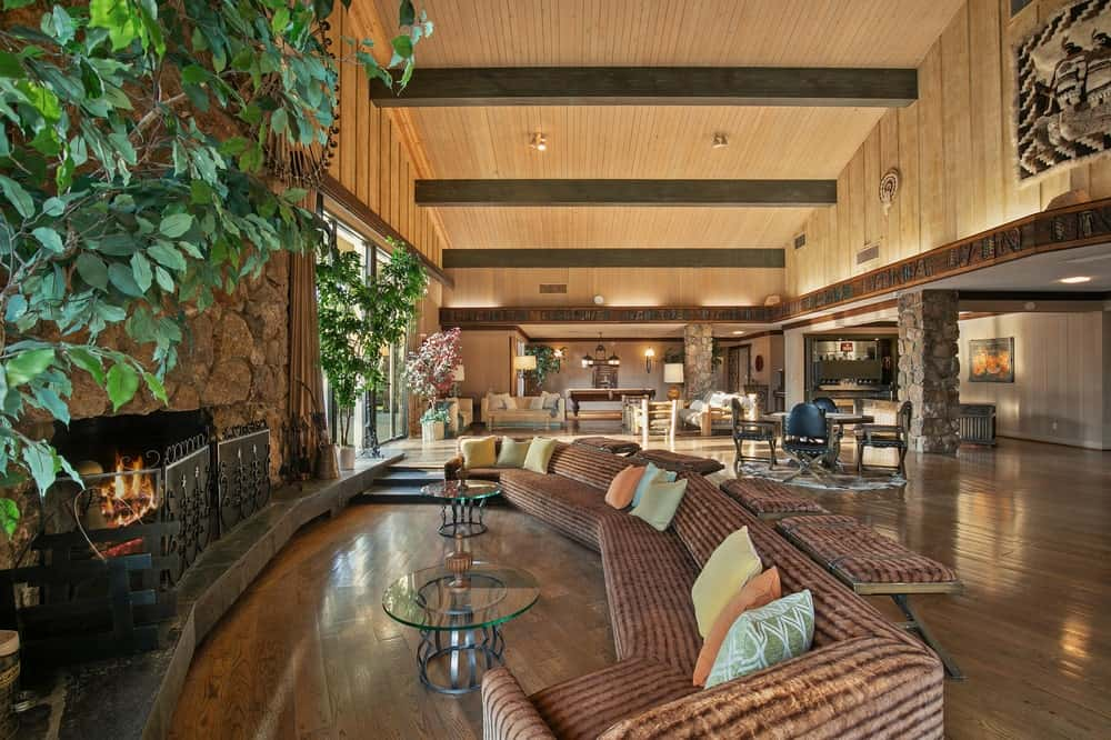 This is a closer look at the curved sectional sofa facing the large stone fireplace along with a glass-top coffee table. Image courtesy of Toptenrealestatedeals.com.