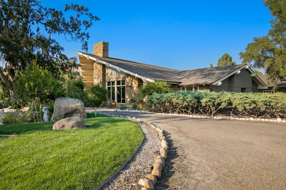 This is the wide driveway and walkway leading to the main lodge flanked with decorative river stones and grass lawn. Image courtesy of Toptenrealestatedeals.com.
