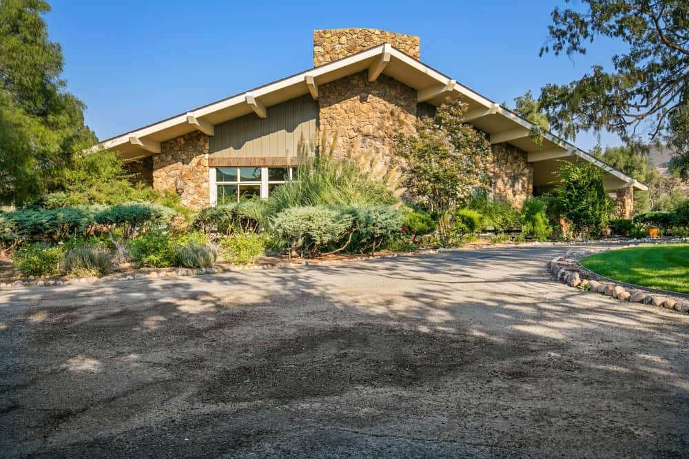 This is the front of the main lodge showcasing the large mosaic stone chimney and the lush landscaping of shrubs and trees on the side. Image courtesy of Toptenrealestatedeals.com.