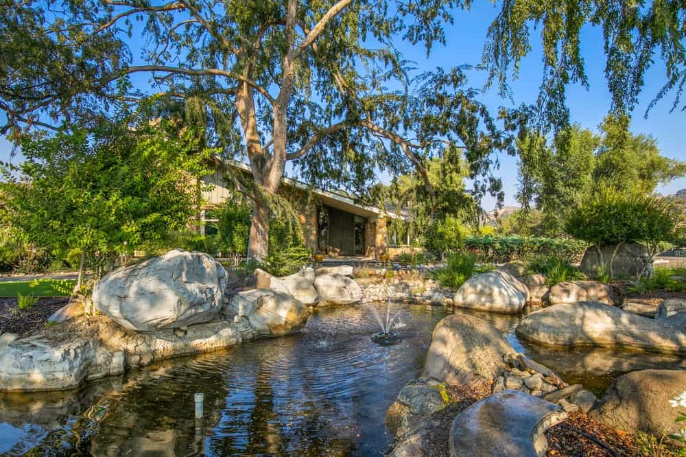 The main lodge is adorned with a pond on the side bordered by mosaic stone walls and lush landscaping. Image courtesy of Toptenrealestatedeals.com.