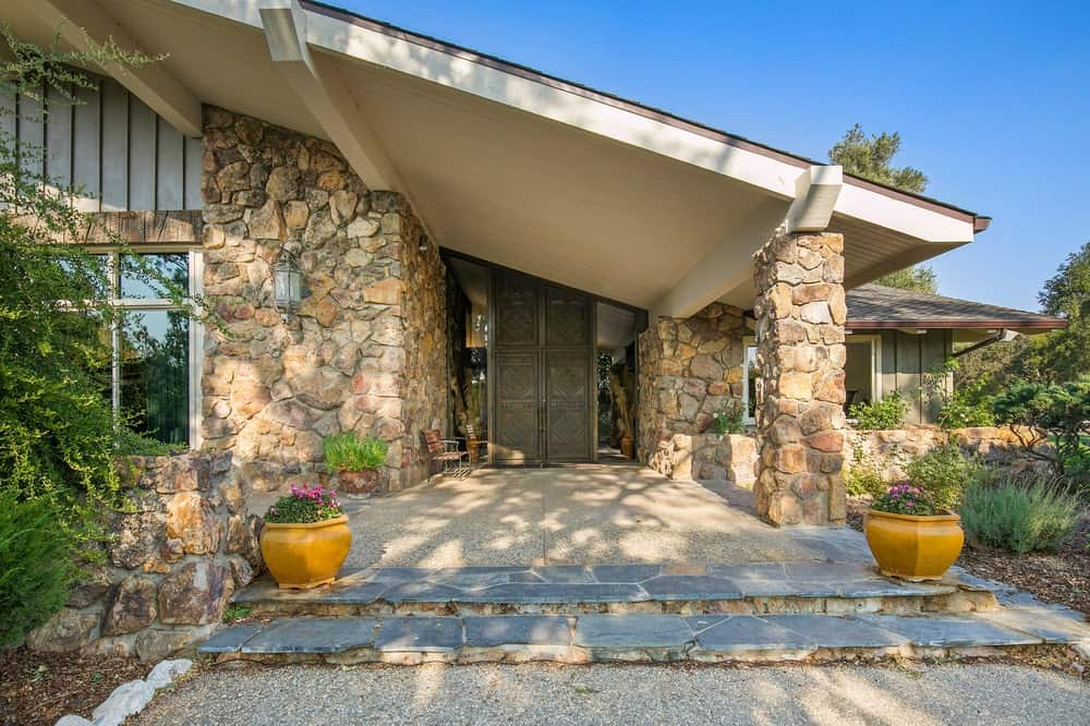 This is the main entrance of the main lodge with a shed ceiling, mosaic stone walls and pillars and a set of concrete steps leading to the walkway adorned by potted plants. Image courtesy of Toptenrealestatedeals.com.