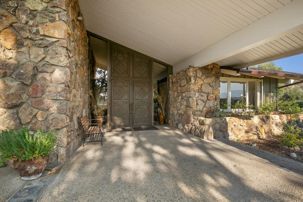This is a close look at the main entrance of the main lodge that has a large wooden main door flanked by glass walls and a bench on the side. Image courtesy of Toptenrealestatedeals.com.