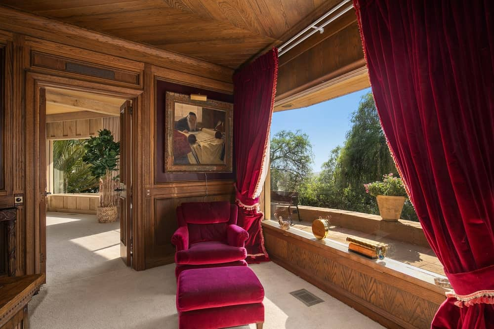 This is the home office that has wood-paneled walls to match the ceiling. These are then complemented by the large window, red armchair and red curtains. Image courtesy of Toptenrealestatedeals.com.