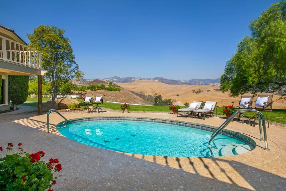 This is the back of the Founder's Building that has a small pool surrounded by lounge chairs and has a nice view of the ranch. Image courtesy of Toptenrealestatedeals.com.