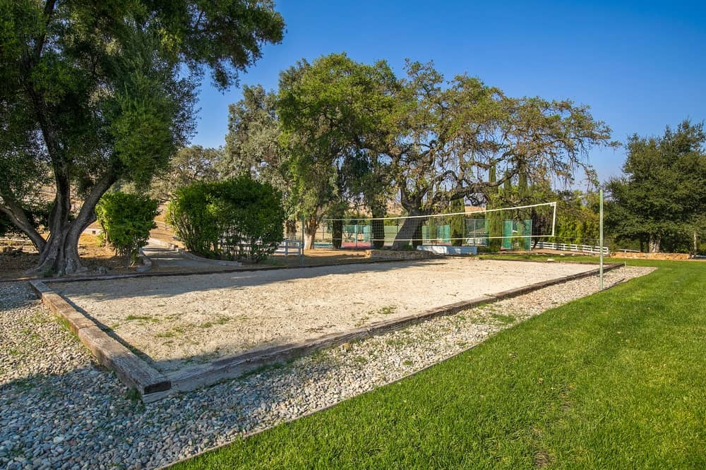 The recreation area also has a volleyball area with sand bordered by graveled soil and grass and shaded by tall trees. Image courtesy of Toptenrealestatedeals.com.
